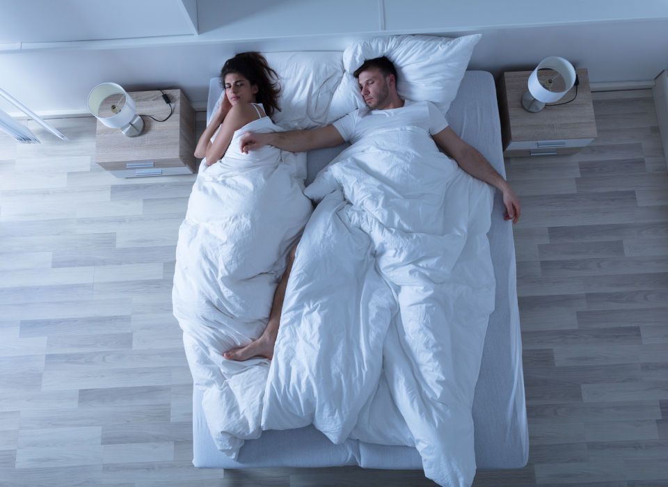 Overhead view of couple laying in bed, the man is asleep, his right arm is on the woman and she looks annoyed